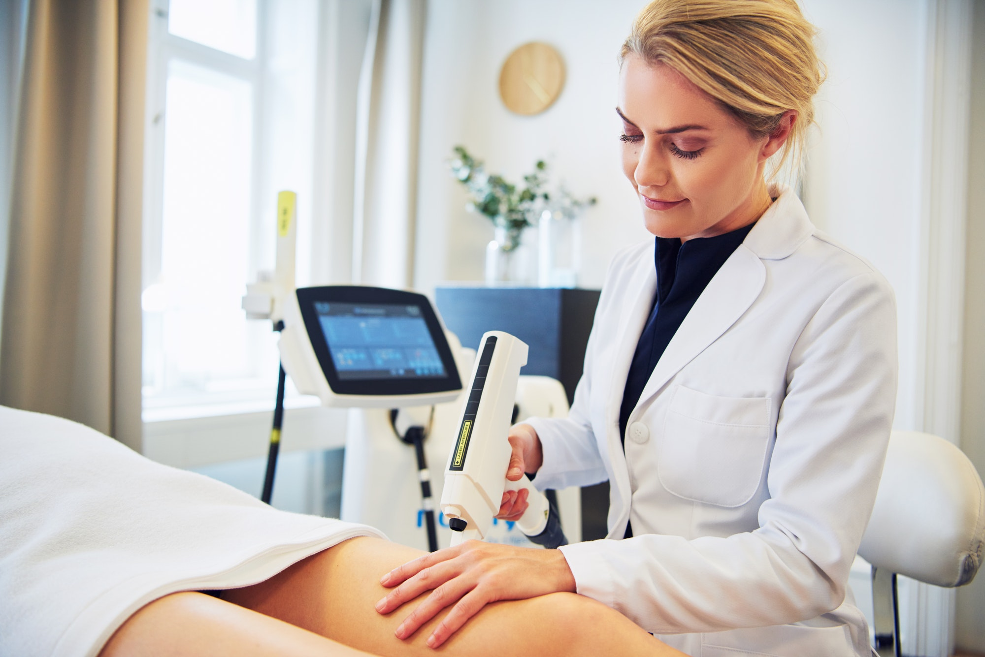 Clinic technician performing electrolysis on a female client's leg